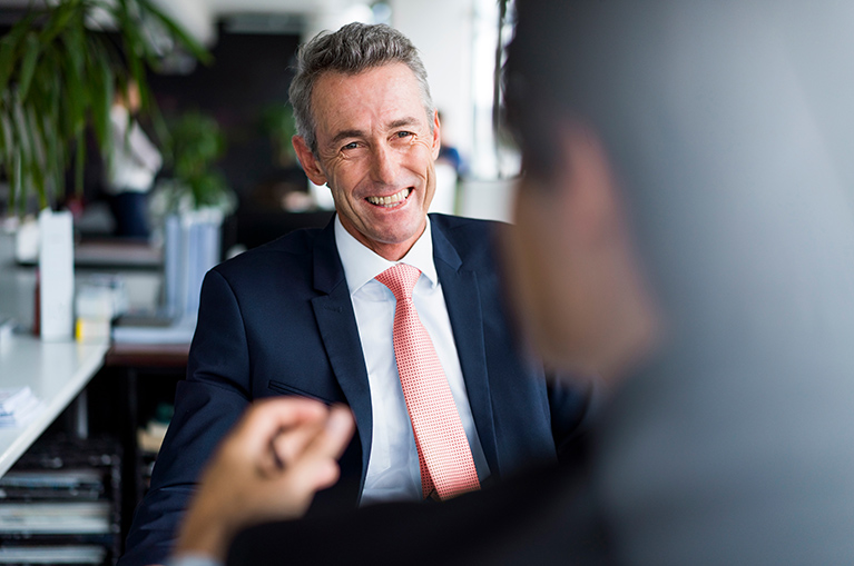 A man smiles at someone sitting across from him during a business meeting.