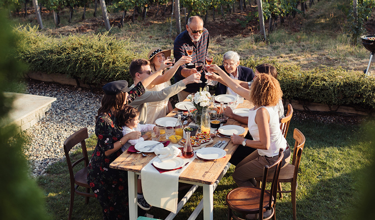 A family toasting around a table in a courtyard.