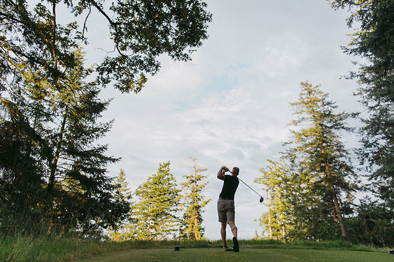 A man hits a ball on a forested golf course.