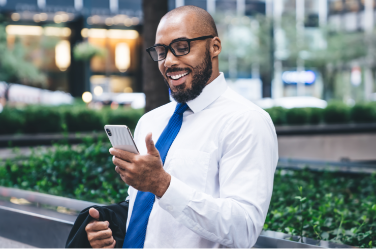 Un jeune conseiller, en chemise et cravate, consultant l'hebdo économique depuis son téléphone intelligent, souriant